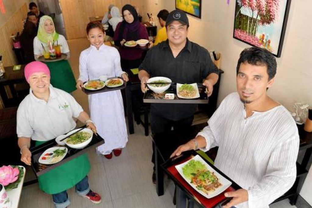 JUADAH BARU JADI SANTAPAN : Encik Jumali (bertopi) dan rakan niaganya, Encik Ramly Djamil (kanan), bersama kakitangan mereka di restoran Pho 4A Vietnamese Cuisine, di Jalan Pisang. – Foto M.O. SALLEH