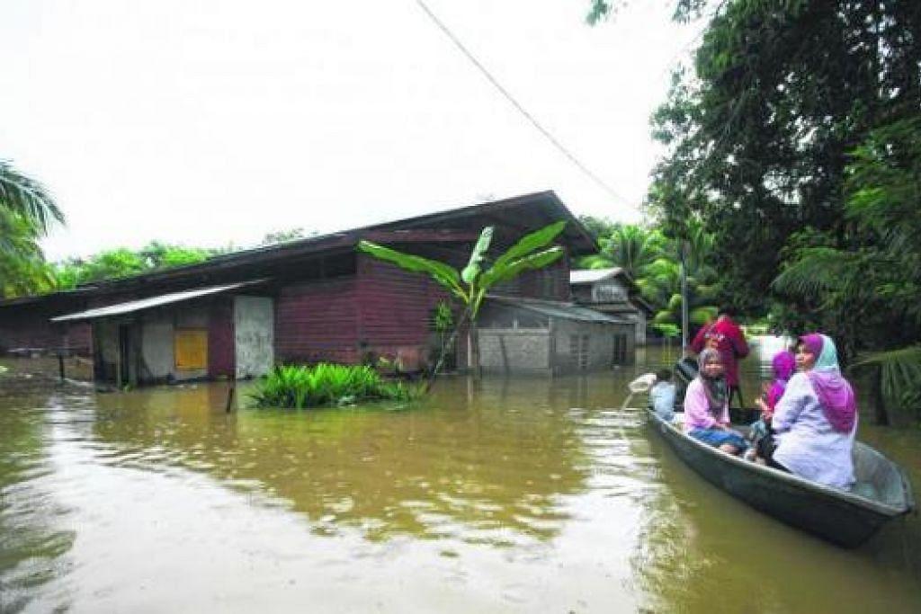 TERJEJAS DEK BAH: Penduduk di kawasan Temerloh, Pahang, terpaksa menggunakan sampan untuk bergerak. - Foto REUTERS