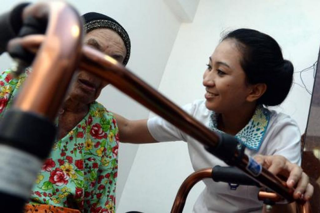 BANTU BERJALAN: Cik A'zizah membantu seorang warga tua berjalan dengan menggunakan tongkat. - Foto TAUFIK A. KADER