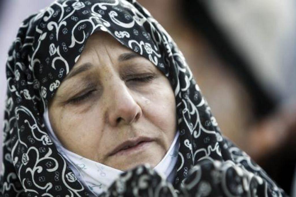 TANGISAN HIBA: Seorang wanita Muslim Iran menitiskan air mata setelah menunaikan solat Aidilfitri di Teheran barat, Selasa lalu. - Foto AFP
