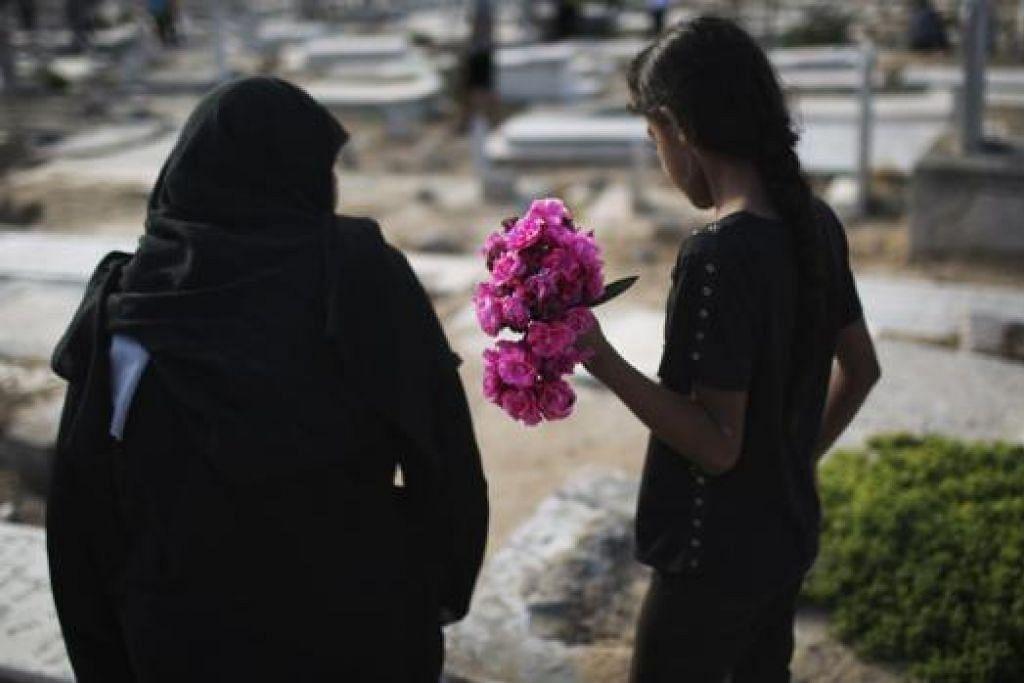 DIKELILINGI KEMATIAN: Seorang wanita dan anak gadis Palestin membawa bunga sewaktu menziarahi kubur keluarga di Bandar Gaza pada Aidilfitri Isnin lalu. - Foto REUTERS