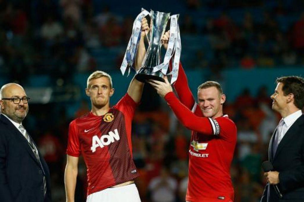 PETANDA KEBANGKITAN UNITED?: Wayne Rooney (kanan), yang dilantik kapten Manchester United, serta Darren Fletcher, menjulang trofi kejuaraan Piala Juara Antarabangsa - kejohanan pramusim yang dianjurkan di Amerika Syarikat - selepas kemenangan ke atas Liverpool semalam. - Foto AFP