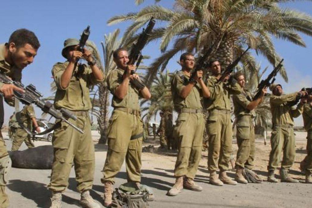 KEADAAN MASIH TEGANG: Askar Israel berhimpun berdekatan sempadan antara Israel dengan Jaluran Gaza sekembali mereka daripada kerahan ke wilayah Palestin kelmarin. - Foto AFP