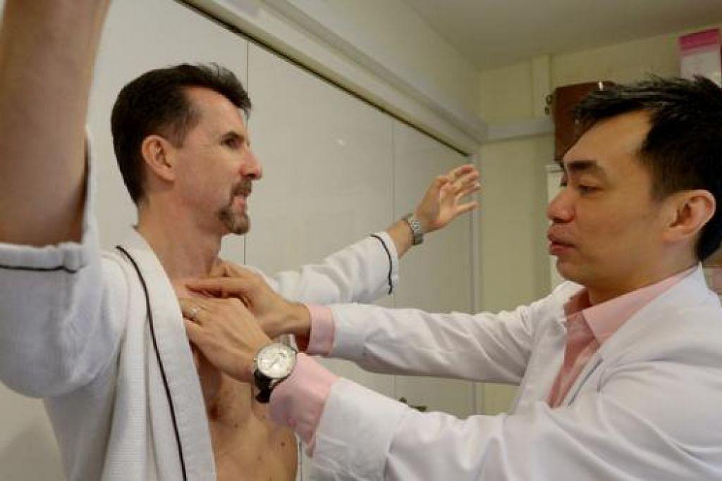 PERIKSA DADA: Mendambakan dada yang sasa merupakan permintaan yang biasa oleh sesetengah kaum Adam, kata Dr Tam (kanan) yang memeriksa dada salah seorang pesakitnya. - Foto TUKIMAN WARJI