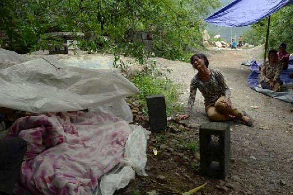 HILANG ORANG TERSAYANG: Seorang wanita meraung di tepi mayat anak lelaki dan perempuannya yang terkorban ekoran gempa yang melanda daerah Ludian, di wilayah Yunnan, Ahad lalu. - Foto-foto AFP