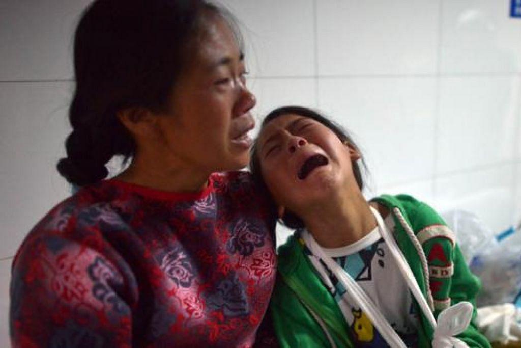 MANGSA GEMPA: Seorang kanak-kanak perempuan tidak tahan sakit sedang dia menunggu giliran berjumpa doktor di sebuah hospital di daerah Ludian. - Foto-foto AFP