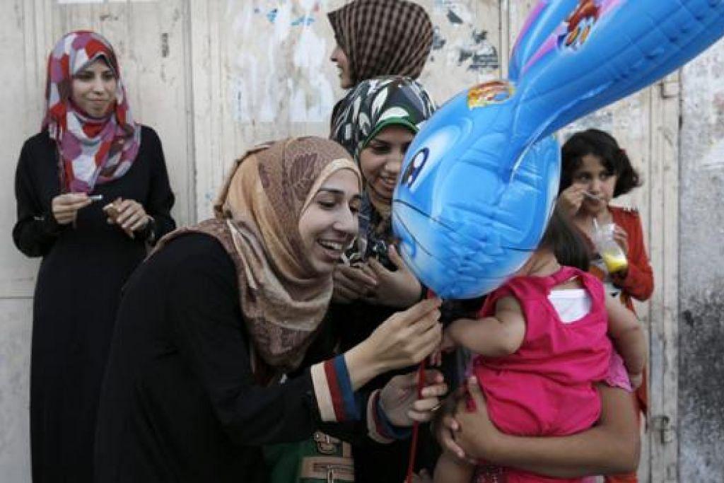 TENANG TAPI TEGANG: Seorang wanita Palestin menghadiahkan belon kepada seorang kanak-kanak semalam sedang penduduk Gaza menghela nafas lega dengan bermulanya gencatan senjata selama 72 jam antara Israel dan Hamas dengan Mesir sebagai orang tengah yang diharapkan akan membawa kepada damai yang berpanjangan. - Foto REUTERS