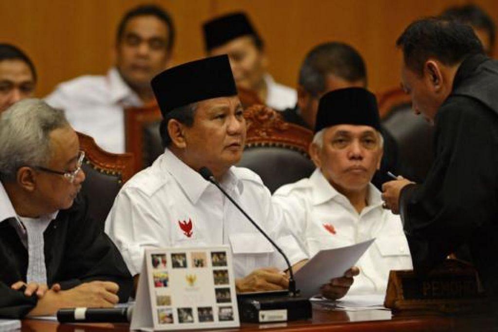 LUAR BIASA: Encik Prabow dan Encik Hatta dilihat berbicara dengan peguamnya sebelum berhujah di Mahkamah Perlembangan Indonesia semalam. Beliau anggap ketiadaan undi bagi pasukannya di 17 pusat mengundi sesuatu yang aneh. - Foto AFP