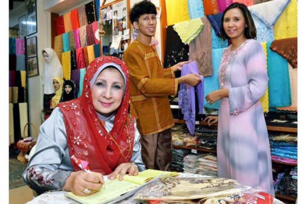 TIDAK PERNAH MENGAKU KALAH: Cik Maimunah Ali (bertudung merah), pemilik Mona J, berani mengambil risiko untuk terus mengekalkan jenamanya. Dua daripada tiga orang anaknya, Encik Janz Abdullah, dan kakaknya, Cik Jihan, kini membantu meneruskan perniagaan ibu mereka. Kededuanya mengenakan pakaian rekaan mereka sendiri. - Foto KHALID BABA