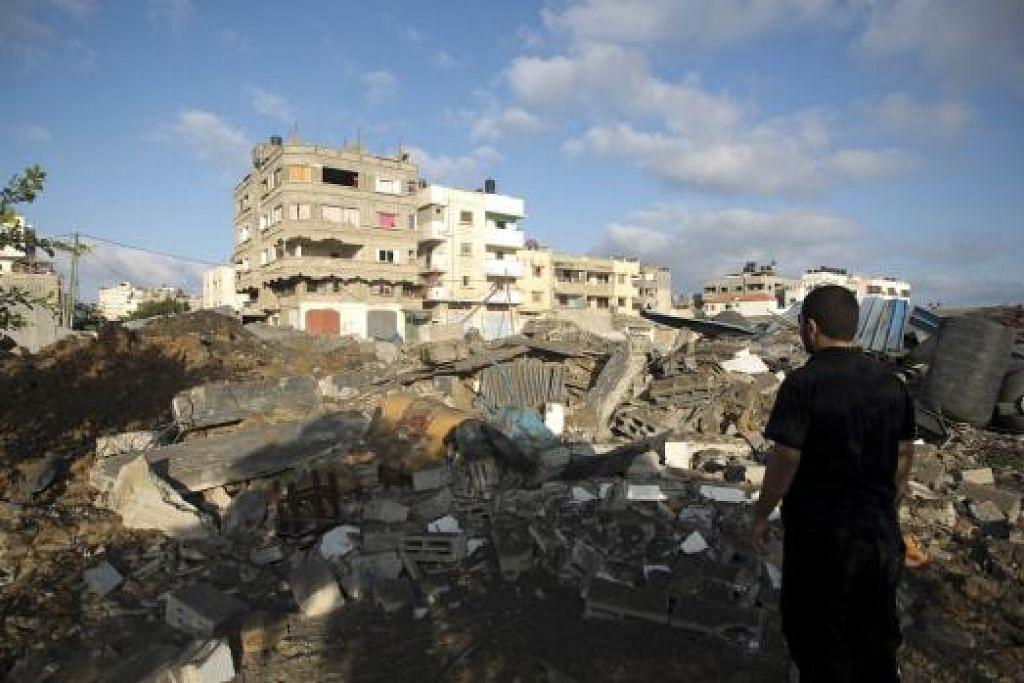 AKIBAT PERANG: Seorang penduduk Gaza melihat kemusnahan yang berlaku setelah kawasan tempatnya dibedil jet pejuang Israel. Lebih 1,800 penduduk Gaza terkorban sementara hampir 10,000 cedera menyusuli serangan Israel ke atas Gaza menyusuli bedilan roket Hamas. - Foto