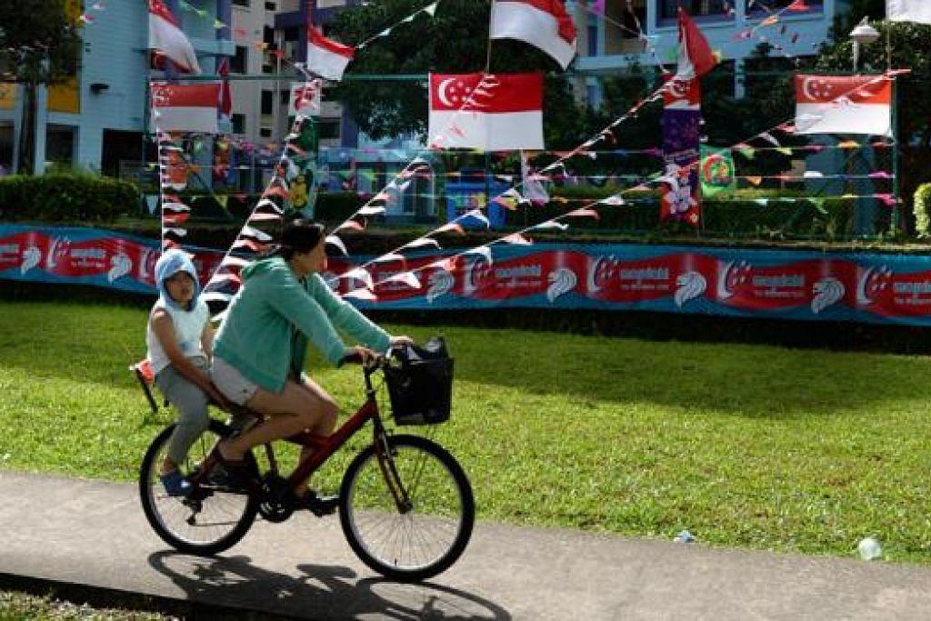 PENUH WARNA-WARNI: Flat HDB ini dan kawasan di sekitar estet perumahan di Singapura  (atas)  dihiasi bendera pelbagai saiz dan kain rentang menjelang Hari Kebangsaan hari ini. - Foto-foto ZAINAL YAHYA