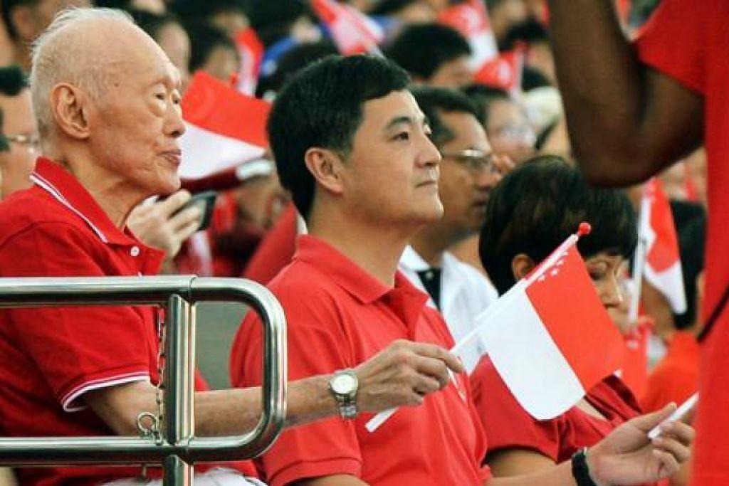 RAIKAN BERSAMA: Mantan Perdana Menteri, Encik Lee Kuan Yew (kiri), yang dilihat duduk di sebelah Menteri Negara Kanan (Pejabat Perdana Menteri), Encik Heng Chee How, sama-sama menyambut Hari Kebangsaan bersama rakyat. Para penonton semua berdiri dan memberi sorakan gemuruh apabila beliau muncul di Pentas Terapug Marina Bay.