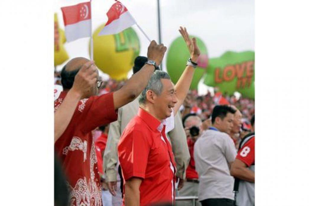 MERAH PUTIH SINGAPURA: Perdana Menteri, Encik Lee Hsien Loong, yang tampil segak dengan kemeja merah putih, melambai ke arah para penonton sebelum ketibaan Presiden Tony Tan.