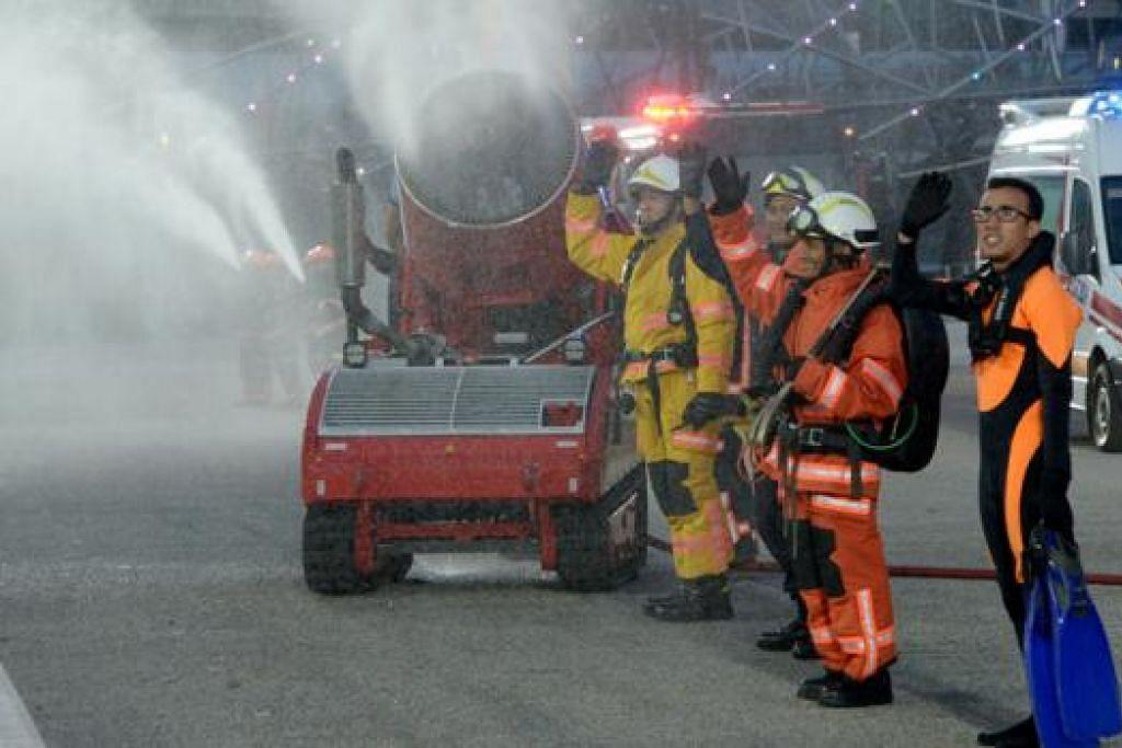 PENONTON TURUT 'MANDI': Pegawai SCDF melambai kepada penonton sementara mesin melawan api kawalan jauh menunjukkan keupayaannya menyembur air setinggi empat tingkat.