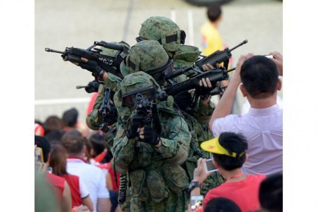 PERAJURIT NEGARA: Penonton menyaksikan anggota tentera SAF dari dekat apabila mereka memasuki ruang penonton di pentas terapung Marina Bay.