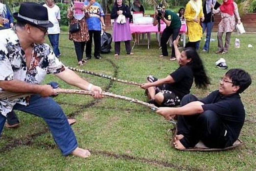MENGEMBALIKAN NOSTALGIA: Antara aktiviti yang dilakukan semasa mengadakan homestay ialah permainan tarik upih. – Foto-foto HAMZAH RAHIM