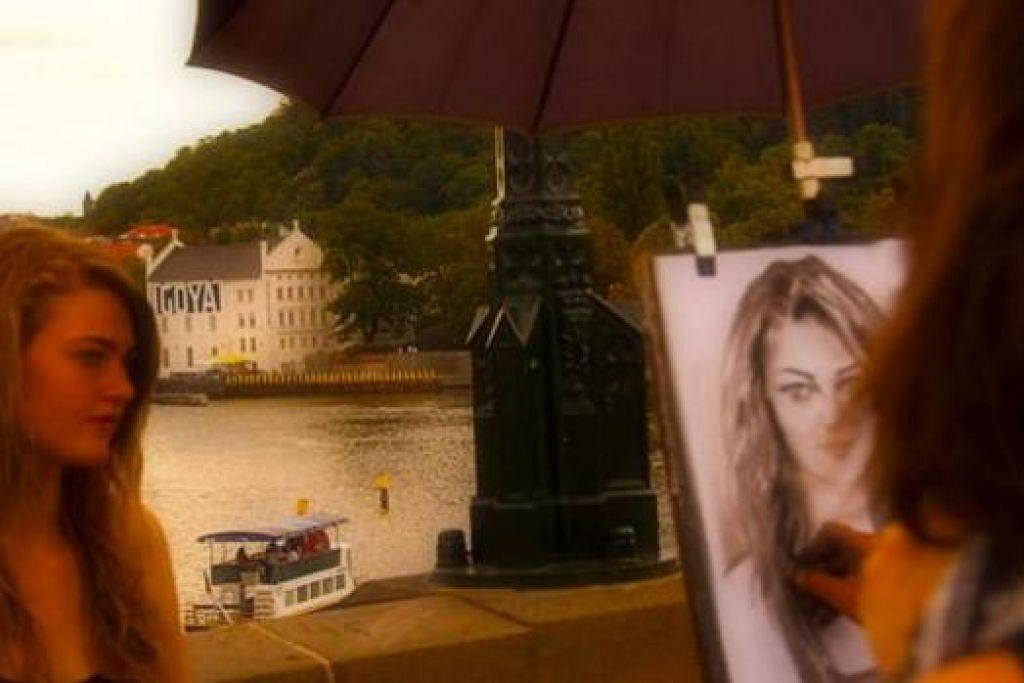 SEINDAH LUKISAN: Anda boleh mendapatkan pelukis untuk melukis potret anda di Jambatan Charles. - Foto-foto MOKSIM SALEH