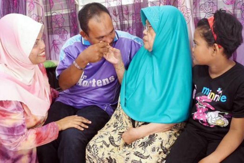 DOA TERMAKBUL: Encik Mohd Hatta bersalam dengan ibunya Cik Patiah di rumah kakaknya di Boon Lay baru-baru ini bersama isterinya, Cik Noryasmin (kiri), dan anak bongsu mereka Nor Qamareena. - Foto JOHARI RAHMAT