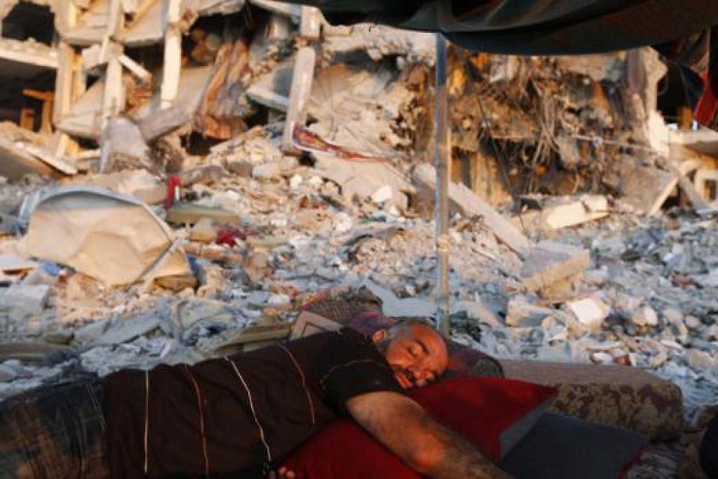 PRASARANA MUSNAH: Seorang lelaki Palestin tidur di bawah khemah di depan apartmennya di bandar Beit Lahiya, di utara Jaluran Gaza, yang ranap ekoran serangan udara Israel. - Foto REUTERS