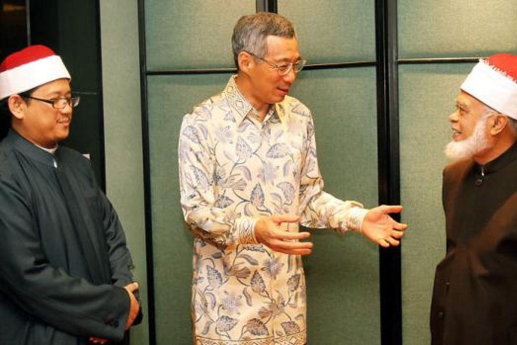 HARGAI SUMBANGAN MUFTI: PM Lee berbual dengan mantan Mufti Syed Isa Semait dalam satu majlis pada 21 Januari 2011. Di sebelah PM ialah Mufti Mohamed Fatris Bakaram.