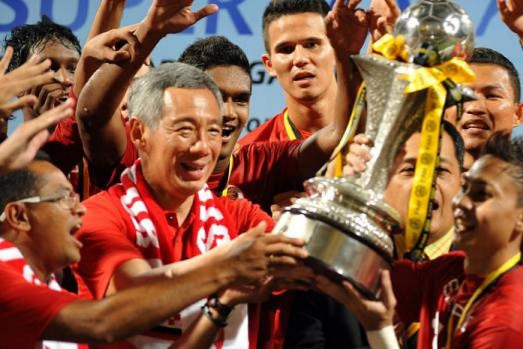 SYABAS JUARA: PM Lee dan kapten LionsXII Shahril Ishak, menjulang Piala Liga Perdana Malaysia selepas LionsXII mengalahkan Felda United 4-0 sekali gus menjadi juara di Stadium Jalan Besar pada 2 Julai 2013.
