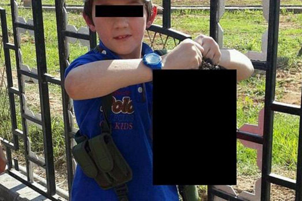 BAGAIKAN TIDAK PERCAYA: Gambar yang diedarkan di laman media sosial ini memaparkan seorang kanak-kanak berusia tujuh tahun dipercayai anak seorang lelaki Australia yang melarikan diri ke Syria memegang kepala seorang askar Syria yang sudah dipenggal. - Foto TWITTER