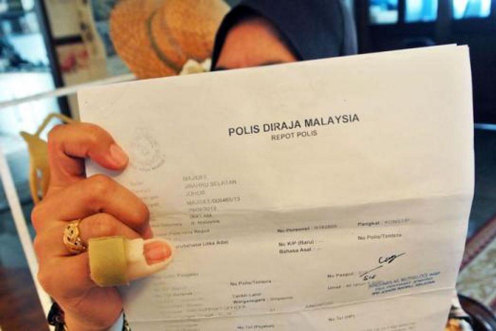 MANGSA LAIN: Seorang warga Singapura yang mahu dikenali sebagai 'Cik Yati' menunjukkan laporan polis yang dibuatnya selepas beliau dirompak di stesen minyak di Johor Bahru tahun lalu. Jari kelengkeng kanannya cedera dalam kejadian itu. - Foto fail