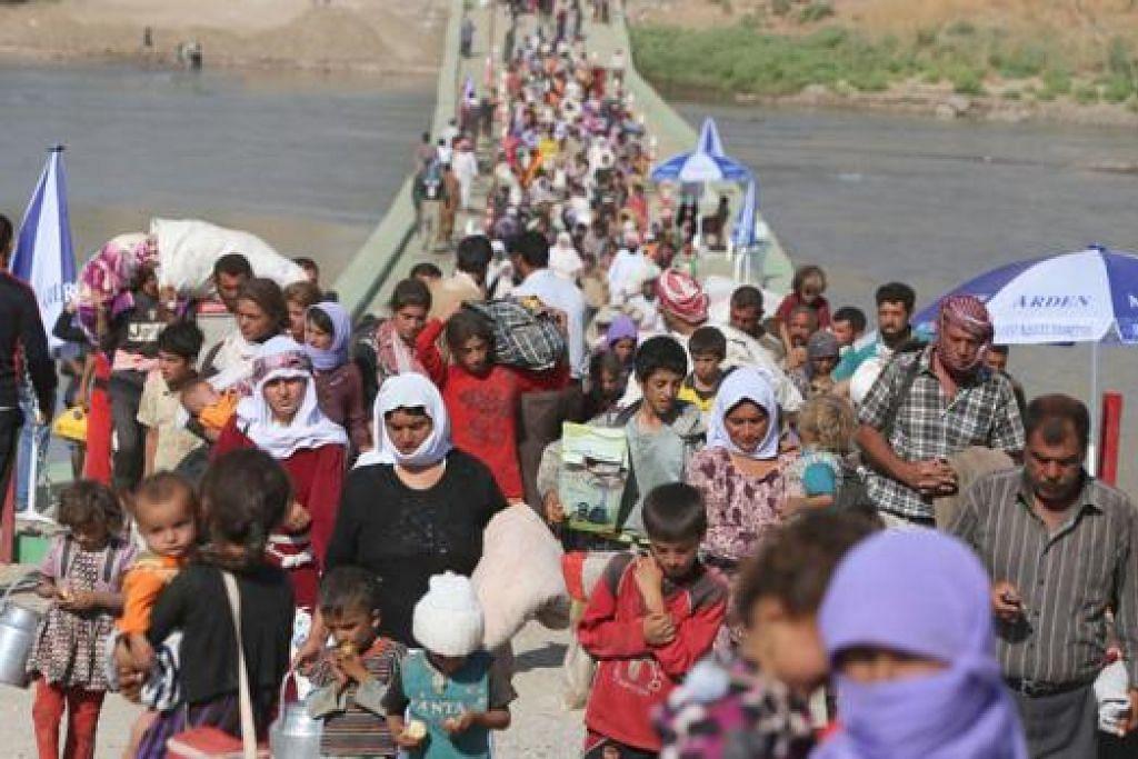 KEHILANGAN TEMPAT TINGGAL: Penduduk Iraq daripada puak Yazidi menyeberangi jambatan Fishkhabur di sempadan Syria-Iraq kelmarin setelah melarikan diri daripada pertempuran. - Foto AFP
