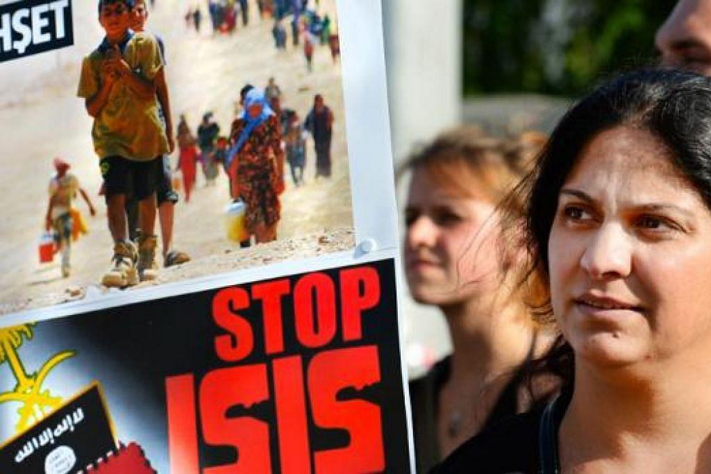 DAPAT BANTAHAN DUNIA: Seorang penunjuk perasaan di Belanda memegang sepanduk menggesa tindakan keganasan ISIS dihentikan. - Foto AFP