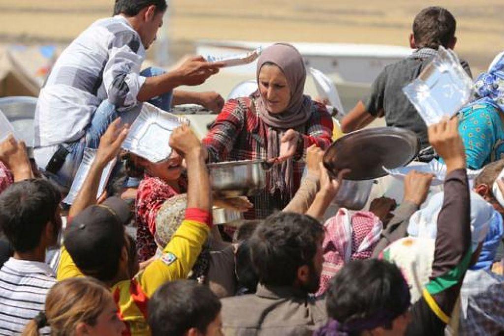 KRISIS KEMANUSIAAN: Pelarian Yazidi dari Iraq berebut mendapatkan bekalan makanan di khemah pelarian Newroz, Syria selepas melarikan diri dari serangan pejuang militan Negara Islam (IS). – Foto AFP