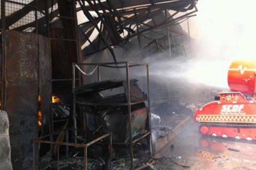 SEMUA HANGUS: Mesin memadam kebakaran ini turut digunakan bagi menangani kebakaran kilang di Sungei Kadut semalam. - Foto SCDF