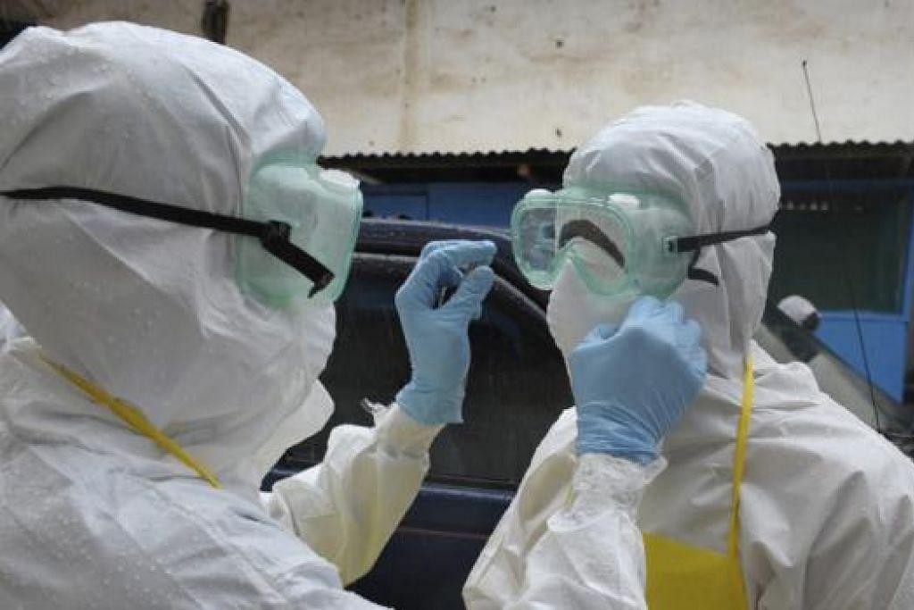 BERHATI-HATI: Kakitangan kesihatan memakai pakaian perlindungan sebelum mengangkat mayat yang disyaki dijangkiti virus Ebola di pasar Duwala, Liberia, kelmarin. - Foto REUTERS