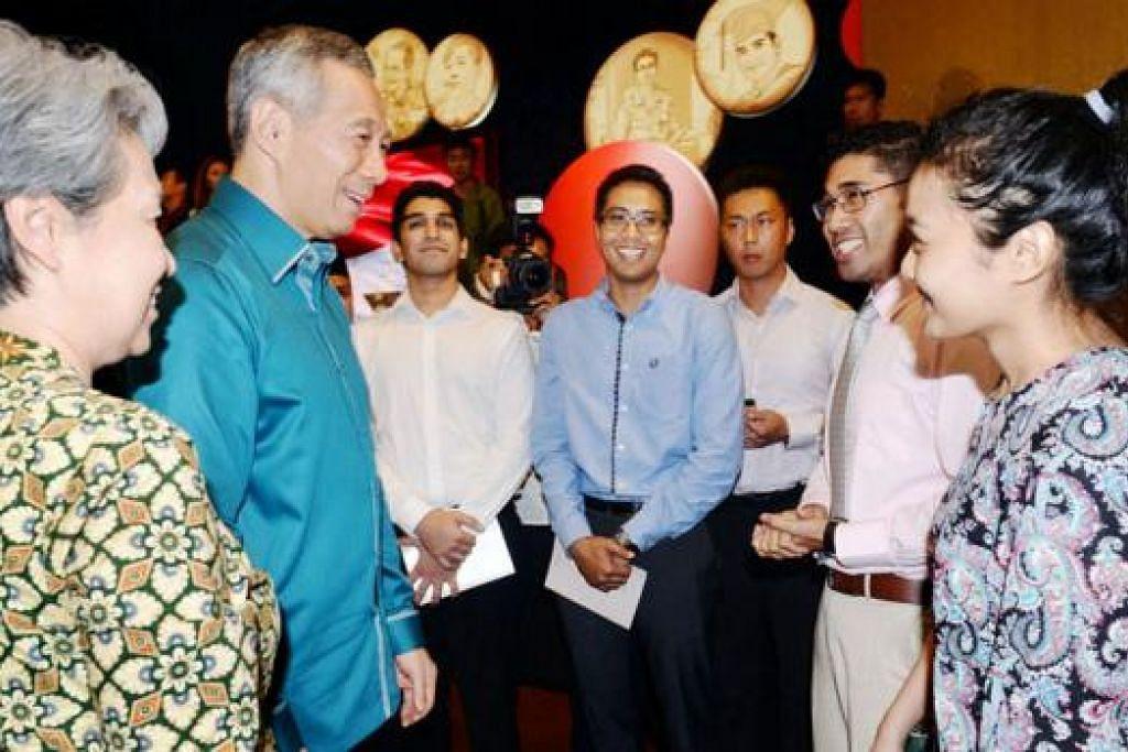 KEJAYAAN MEMBANGGAKAN: Perdana Menteri Lee Hsien Loong (dua dari kiri) bersama isterinya, Cik Ho Ching, berbual dengan siswazah cemerlang - antaranya ialah Encik Afzal Ali (tiga dari kiri), Encik Faizal Abdul Aziz (dua dari kanan) dan Cik Fauziah Ally.