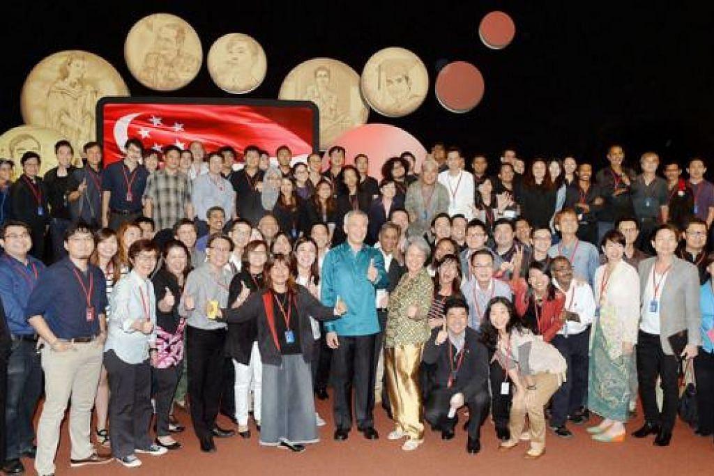 BELAKANG TABIR: Encik Lee bergambar bersama kumpulan yang menjayakan Rapat Hari Kebangsaan 2014, yang antaranya terdiri daripada kakitangan Pejabat Perdana Menteri (PMO), Kementerian Perhubungan dan Penerangan (MCI), Politeknik Nanyang dan MediaCorp. - Foto-foto JOHARI RAHMAT dan TAUFIK A. KADER