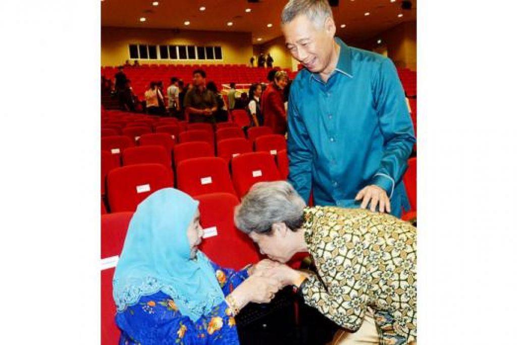 BERI HORMAT: Isteri Perdana Menteri Lee Hsien Loong, Cik Ho Ching, tunduk dan mencium tangan Puan Noor Aishah yang hadir di Rapat Hari Kebangsaan kelmarin. - Foto JOHARI RAHMAT