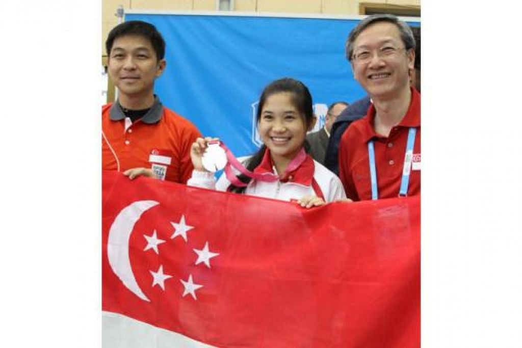 KEBANGGAAN NEGARA: Peserta muda menembak negara, Martina Lindsay Veloso, menunjukkan pingat perak yang dimenanginya semalam - pingat sulung Singapura dalam temasya Sukan Olimpik Belia (YOG) yang kini berlangsung di Nanjing, China. Kejayaannya disaksikan oleh Menteri Tenaga Manusia, Encik Tan Chuan-Jin (kiri), dan Menteri Negara, Encik Sam Tan, yang kini berada di Nanjing. - Foto SNOC