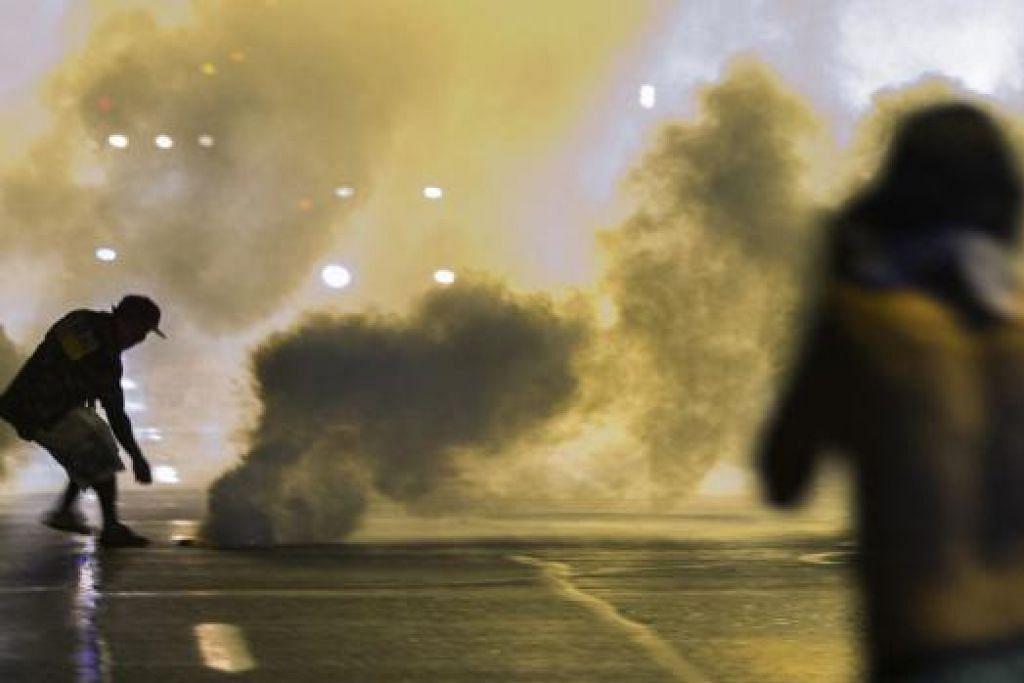 BANTAH: Penunjuk perasaan di bandar Ferguson, Missouri, bertempur dengan polis yang menggunakan gas pemedih mata. Penunjuk perasaan membantah penembakan Encik Michael Brown, seorang penduduk kulit hitam, oleh seorang pegawai polis berkulit putih. - Foto REUTERS
