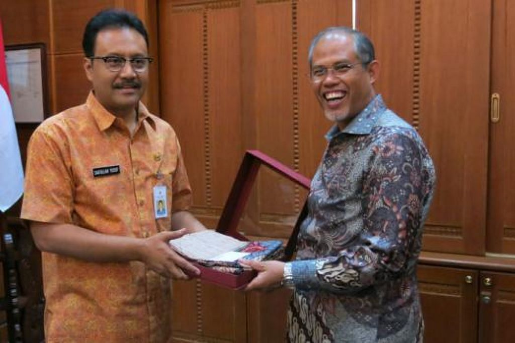 TANDA MUHIBAH: Drs Saifullah (kiri) memberikan sehelai kain batik kepada Encik Masagos di akhir pertemuan mereka semalam. - Foto MFA
