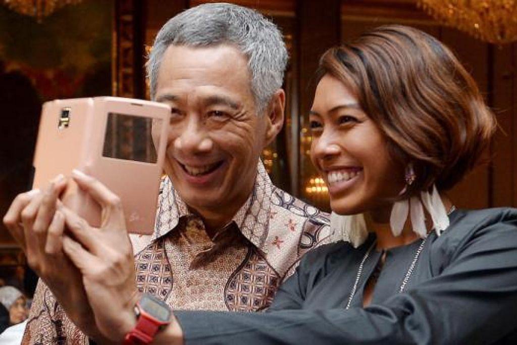 JAUHARI HARAPAN BER-SELFIE: Cik Aisyah mengambil peluang bergambar selfie dengan Perdana Menteri, Encik Lee, di majlis penyampaian Anugerah Jauhari kelmarin. - Foto TAUFIK A. KADER