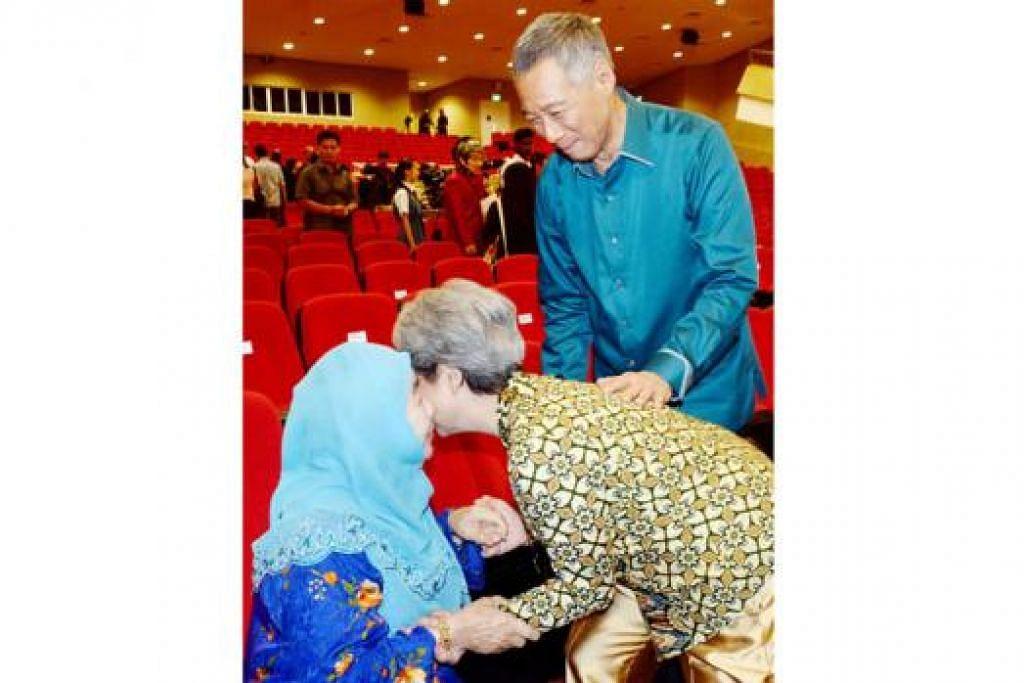TUNJUK HORMAT: Cik Ho Ching, isteri Perdana Menteri, bukan sahaja mencium pipi (atas), malah mencium juga tangan Puan Noor Aishah Mohd Salim isteri presiden pertama Singapura, Allahyarham Yusof Ishak, sebagai menghormati beliau selepas Rapat Hari Kebangsaan, Ahad lalu. Perdana Menteri Lee Hsien Loong pula memerhatikan. - Foto-foto JOHARI RAHMAT