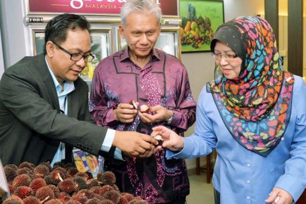 KONSEP 'FRUCERANT': Pengurus Agrobazaar, Encik Mohamad Shukri Ahmad, memberi buah pulasan segar yang dijual untuk dicuba Dato' Husni dan Cik Sharifah. - Foto KHALID BABA