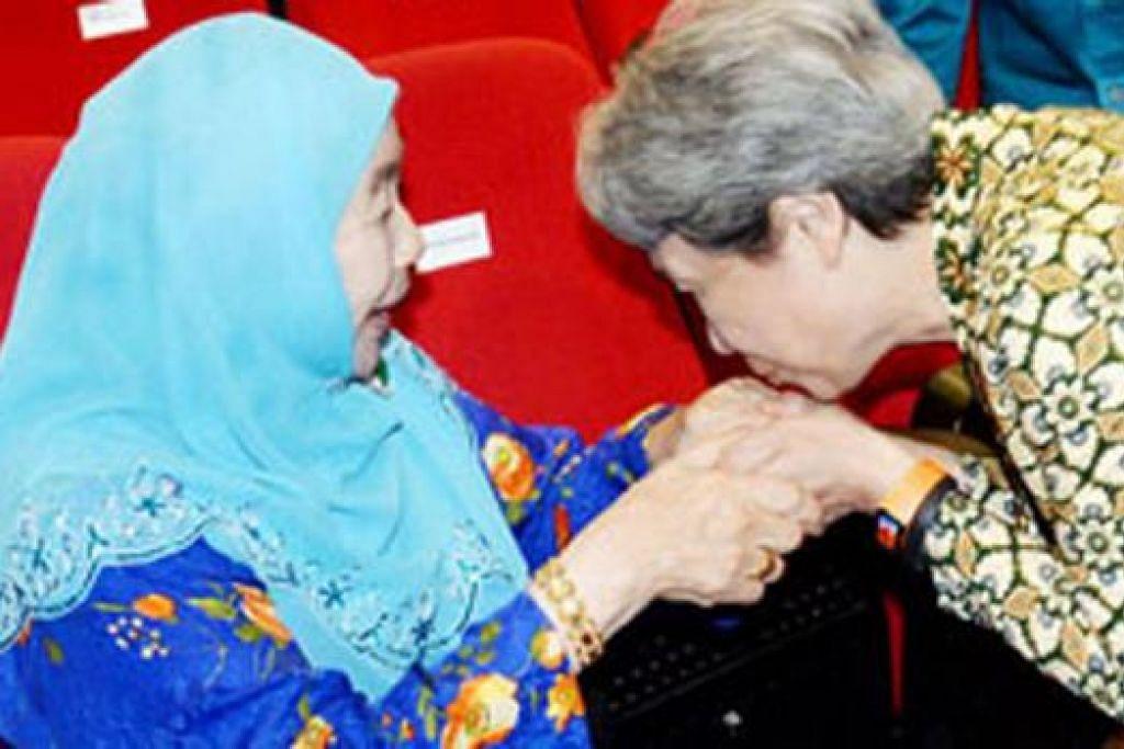 TUNJUK HORMAT: Cik Ho Ching, isteri Perdana Menteri, bukan sahaja mencium pipi, malah mencium juga tangan Puan Noor Aishah Mohd Salim (atas), isteri presiden pertama Singapura, Allahyarham Yusof Ishak, sebagai menghormati beliau selepas Rapat Hari Kebangsaan, Ahad lalu. Perdana Menteri Lee Hsien Loong pula memerhatikan. - Foto-foto JOHARI RAHMAT