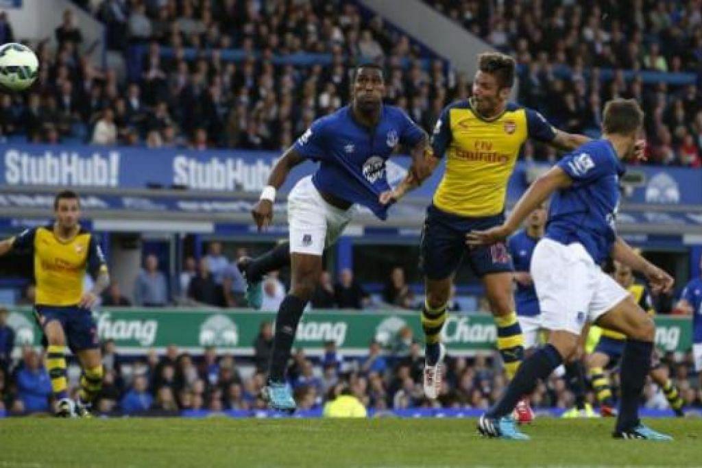 TEPAT KE SASARAN: Penyerang Arsenal, Olivier Giroud (kanan, jersi kuning), melompat tinggi bagi menanduk gol yang menyelamatkan pasukannya semasa seri 2-2 dengan Everton. - Foto REUTERS