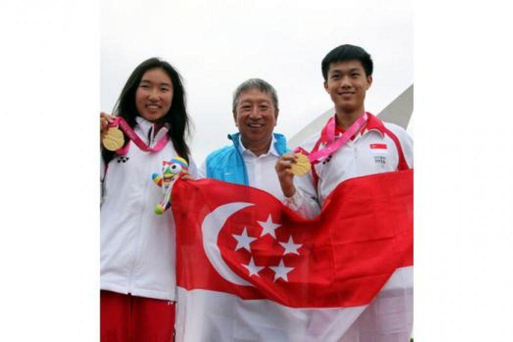 KEJAYAAN PENUH BERSEJARAH: Dua jaguh muda kapal layar, Bernie Chin (kanan) dan Samantha Yom bergambar dengan anggota IOC, Encik Ng Ser Miang, selepas kejayaan mmenangi pingat emas pertama Singapura di Sukan Olimpik Belia (YOG) yang kini berlangsung di Nanjing, China. - Foto SNOC