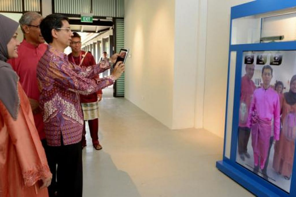 CARA BARU CUBA BAJU: Profesor Faishal (memegang kamera) 'mencuba' pakaian tradisional Melayu di alam maya yang dicipta A*Star sempena rumah terbuka Hari Raya TWM.