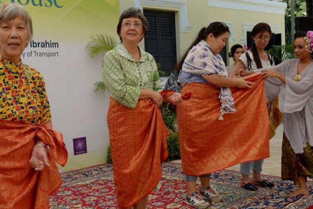 KENALI BUDAYA MELAYU: Para pelawat asing (gambar) yang melawat acara rumah terbuka TWM kelmarin mempelajari cara mengikat kain samping. - Foto-foto TUKIMAN WARJI