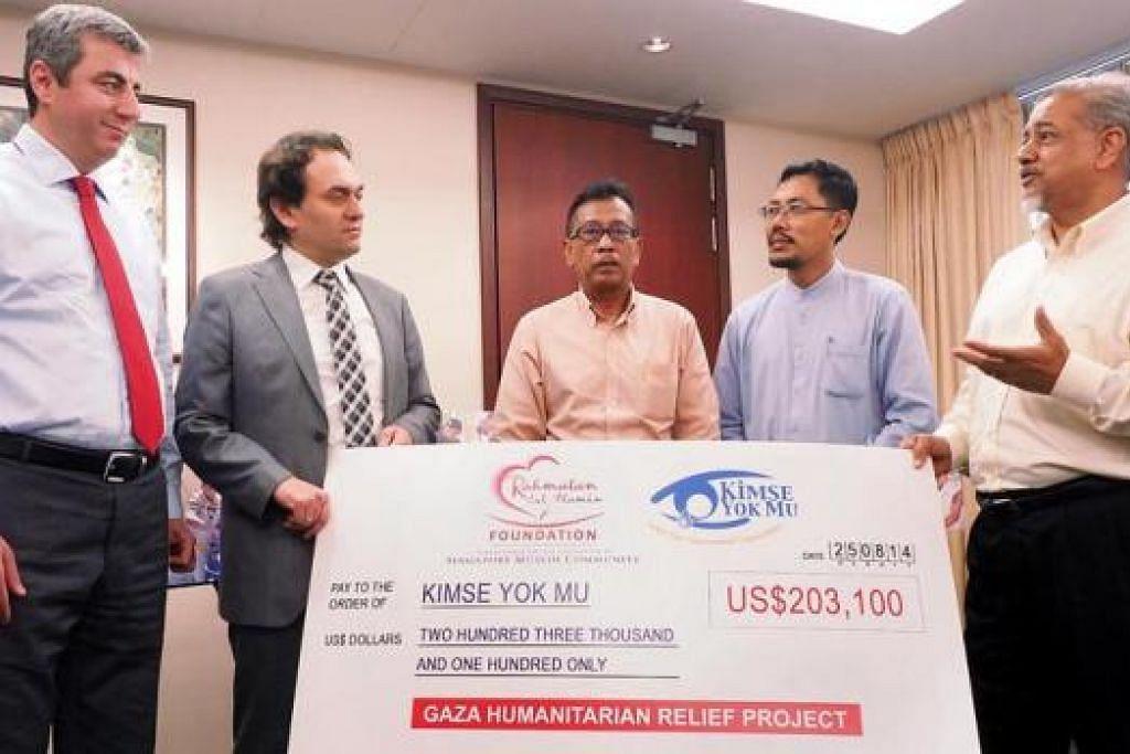 SUMBANGAN MASYARAKAT SINGAPURA: (Dari kanan) Encik Zainul Abidin Ibrahim; Pengarah Masjid, Majlis Ugama Islam Singapura (Muis), Encik Mohamad Helmy Mohd Isa; dan Pengerusi Jawatankuasa Masjid-Masjid Yayasan Rahmatan Lil Alamin (RLAF), Haji Paiman Supangat; menyampaikan cek bernilai AS$203,100 ($253,945) kepada (dari kiri) Naib Pengurus Besar Kimse Yok Mu (KYM), Encik Huseyin Fazlioglu; dan Setiausaha Agung KYM, Encik Savas Metin; semalam. - Foto JOHARI RAHMAT