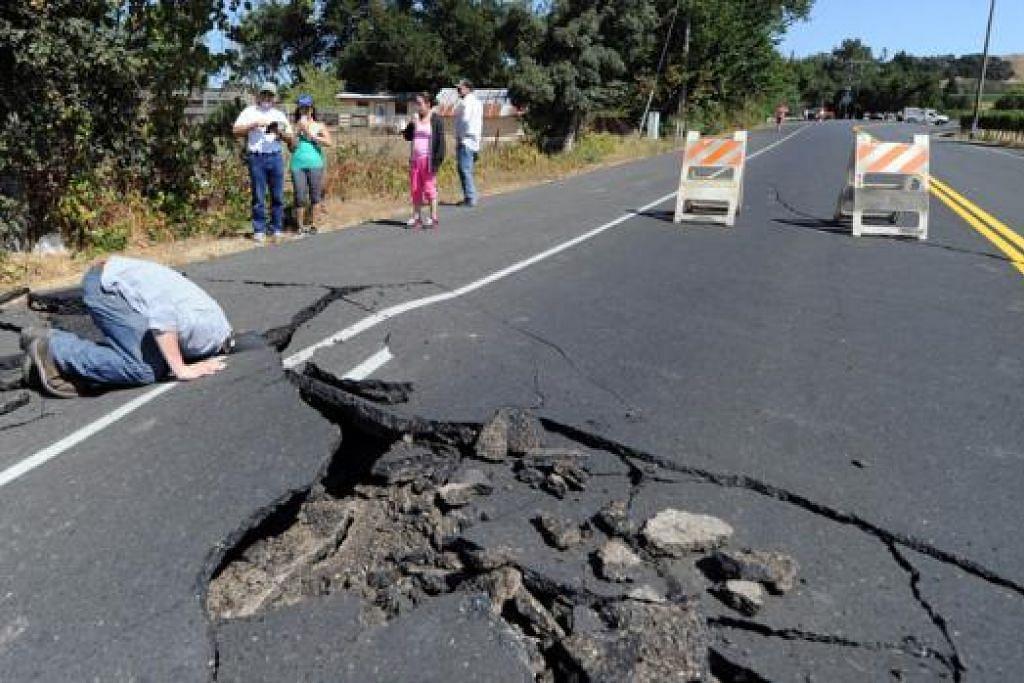 JALAN RAYA 'TERBONGKAR': Penduduk memerhati kerosakan teruk berlaku pada jalan raya yang menyebabkan lebuh raya terpaksa ditutup. Gegaran kuat 6 magnitud yang melanda California turut menjejas 64,000 penduduk wilayah itu. - Foto-foto AFP