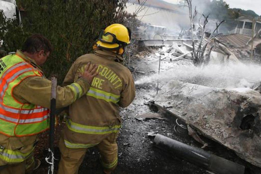 PUNAH: Anggota bomba Daerah Napa menyemburkan buih bagi memadam api dan bara yang membakar rumah mudah alih selepas gempa bumi melanda di California. Banyak bangunan dan rumah rosak teruk.