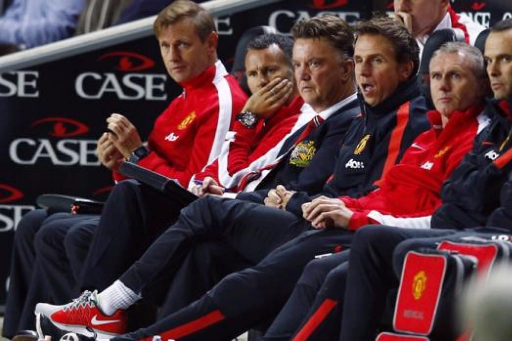 SUASANA MURAM: Pengurus Manchester United, Louis van Gaal (tiga dari kiri), serta pembantunya, Ryan Giggs (di kanannya), menyaksikan pasukan mereka dibelasah kelab yang bermain dalam Divisyen Tiga, MK Dons.